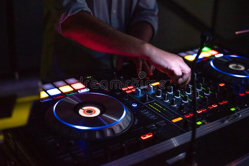 DJ desk in a nightclub party with hands. Studio DJ equipment glowing with light stock images