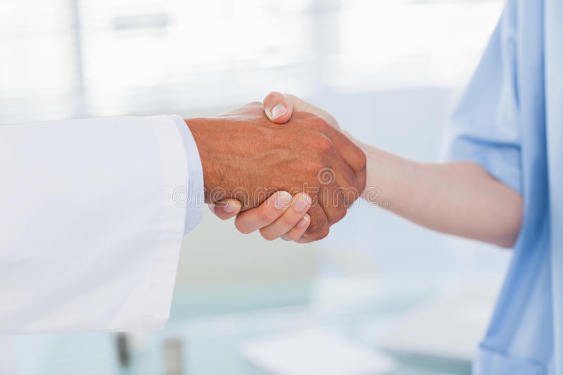 Hands of a doctor and nurse shaking hands stock photography