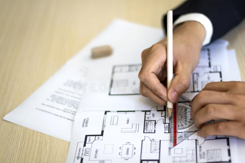 Hands Drawing House Plan on Desk royalty free stock image