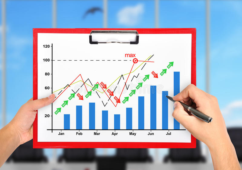 Hands drawing stock chart. In red clipboard stock photo