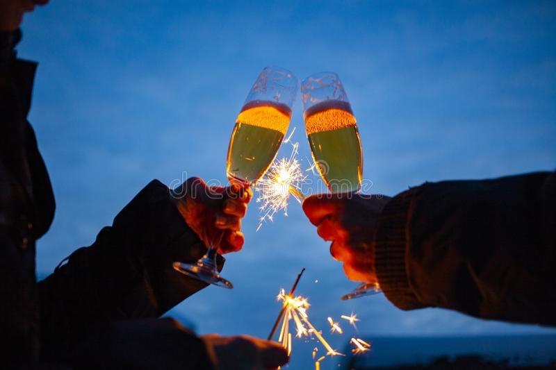 hands of elderly couple holding sparkles and glasses of champagne celebrating New Year stock image