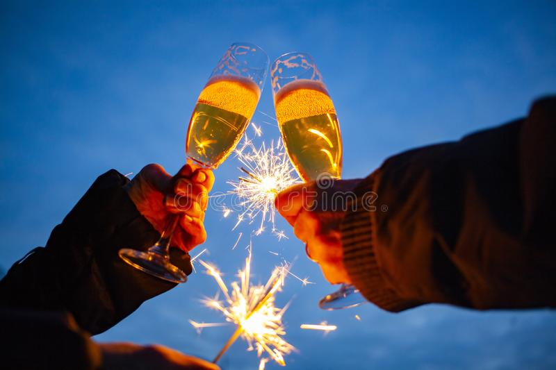 hands of elderly couple holding sparkles and glasses of champagne celebrating New Year royalty free stock photos