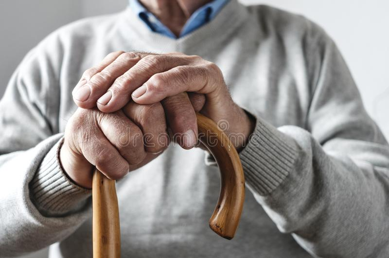 Hands of an elderly man resting on a walking cane. Close up details of the folded hands of an elderly man resting on a walking cane in a mobility and health royalty free stock image