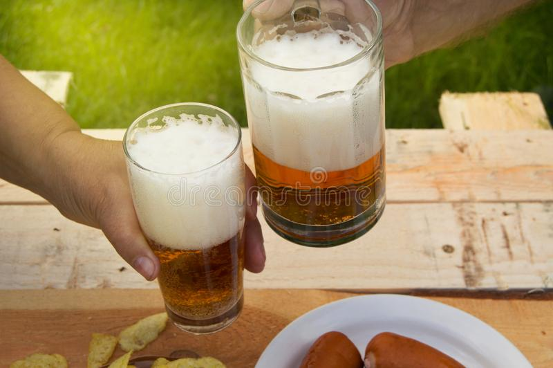 Hands of elderly men and women holding glasses of beer, chips and sausages lie on light wooden boards, people relax on weekends,. October festival royalty free stock photography