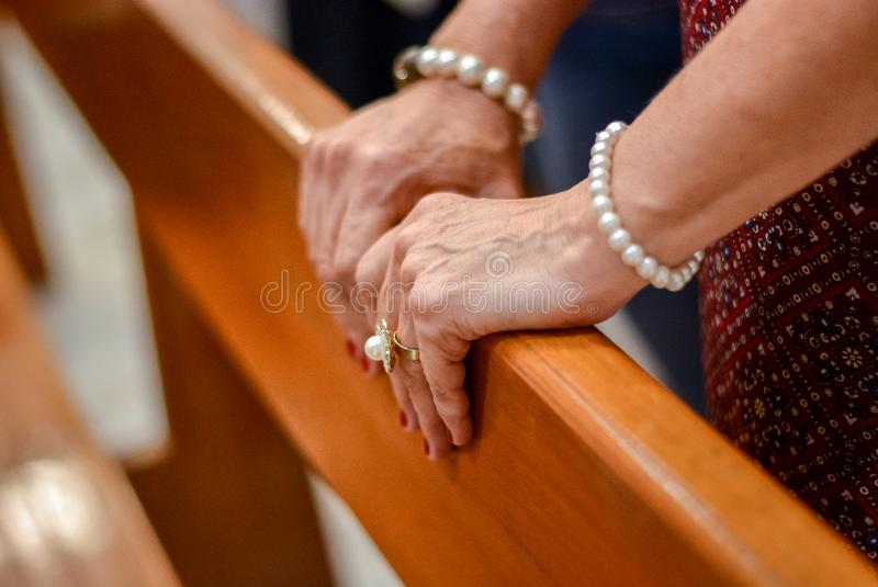 Hands of an elderly woman with bracelets made of pearls royalty free stock image