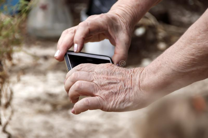The hands of an elderly woman with a mobile phone royalty free stock photos