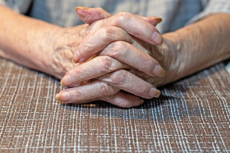 Hands of an elderly woman resting on the table. Parkinson stock photo