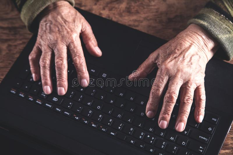Hands of elderly woman typing on keyboard stock photo