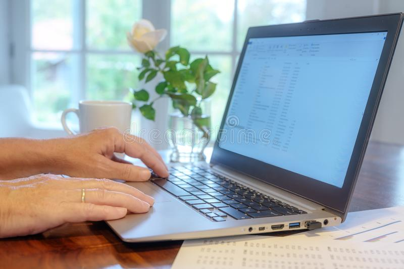 Hands of an elderly woman are working on a laptop in the home office to calculate taxes of her small business stock images