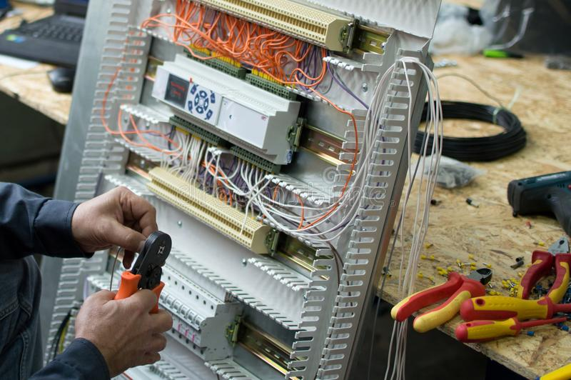 Hands of electrical technician assembling low voltage industrial HVAC control cubicle in workshop. Close-up photo. stock photos