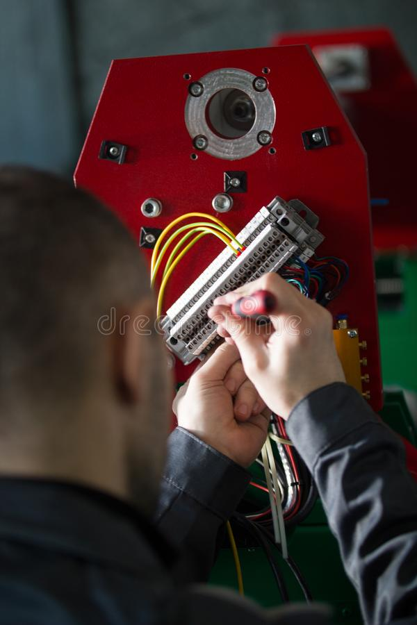 Hands of electrician engineer screwing and testing equipment in fuse box royalty free stock photo