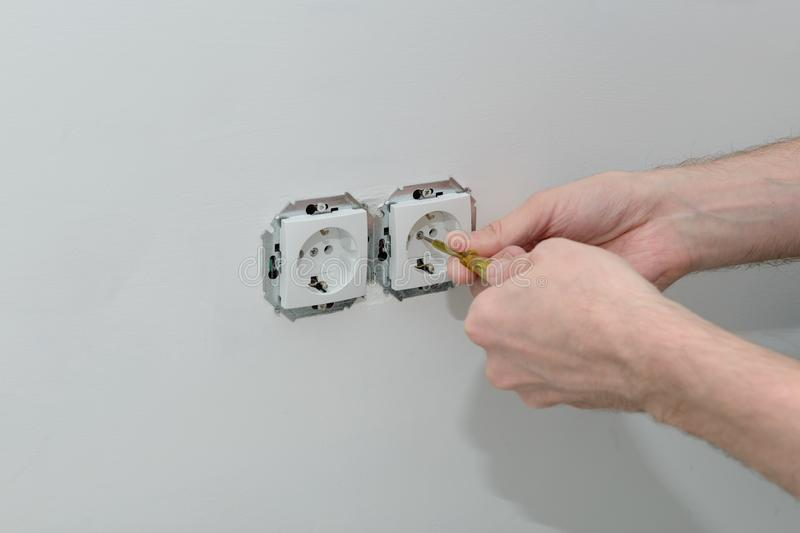 Hands of an electrician install sockets stock photography