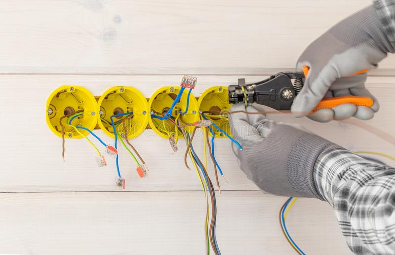 Hands of electrician installing electrical socket with screwdriver in the wall. In new wooden house royalty free stock photography