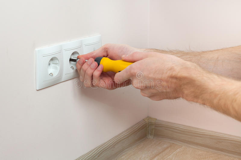 The hands of an electrician installing a wall power socket. royalty free stock photography