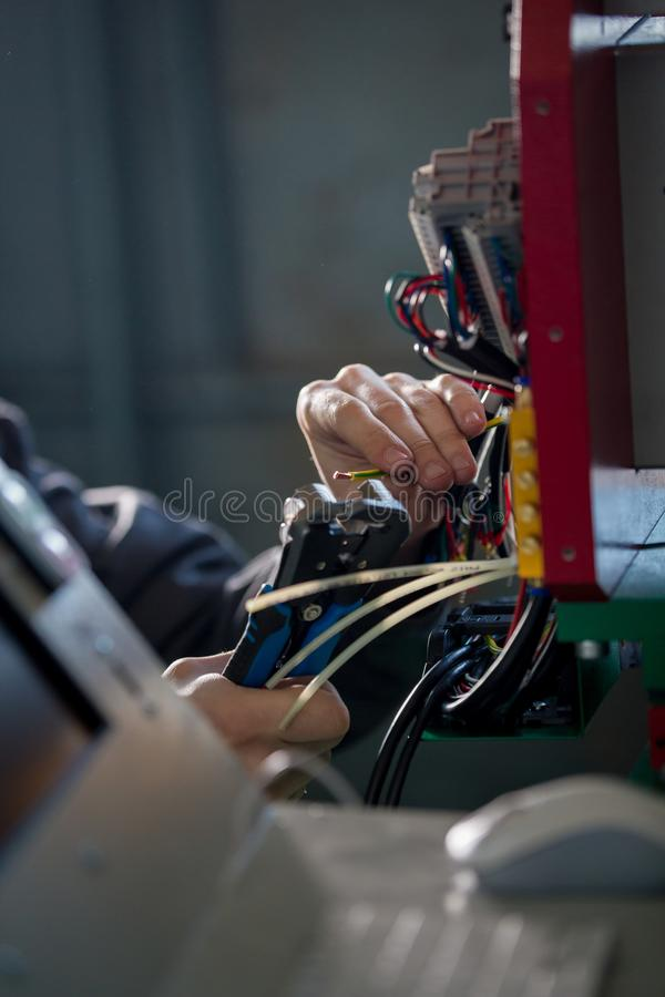 Hands of electrician with stripper installing energy system on machinery industry stock photography