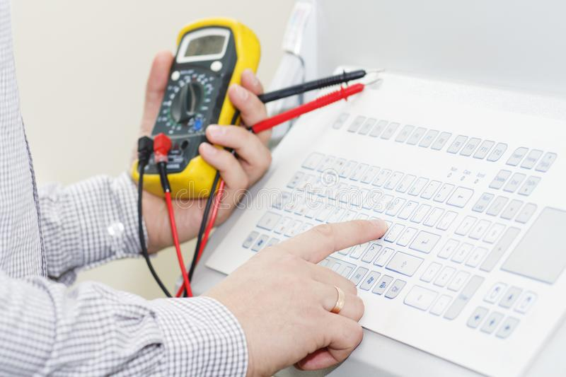Hands of engigeer on control panel of industrial equipment closeup. Engineer with multimeter adjusts technology process royalty free stock images
