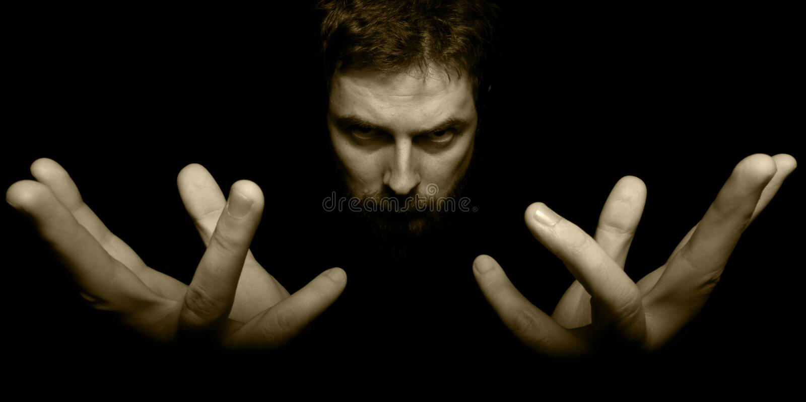 Hands and face of evil magician in the dark stock photos