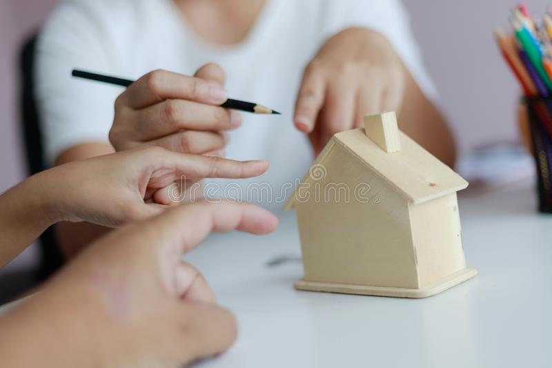 Hands of family father mother and daughther pointing to wooden house model metaphor dream for home building and decoration or. Saving money for real estate royalty free stock photos