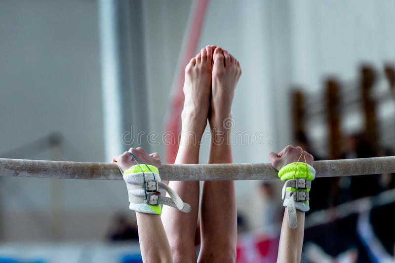 Hands and feet young girl gymnast. Exercises on bar royalty free stock photos