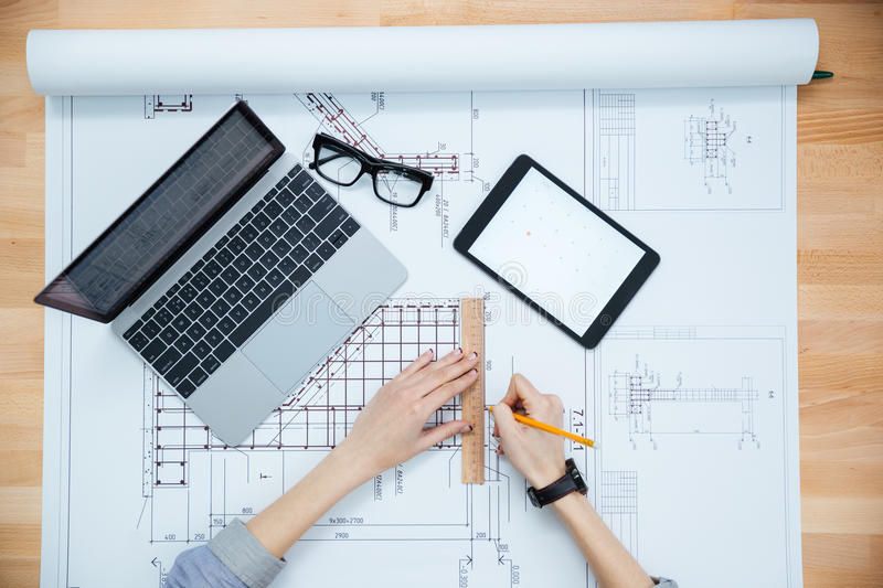 Hands of female architect drawing blueprint royalty free stock image