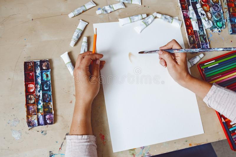 Hands of female artist painting with watercolor paints and colored pencils stock image