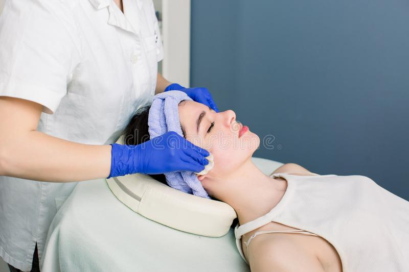 Hands of female beautician cleanses the skin with cotton pads. Facial skincare. Caucasian woman on a cosmetology royalty free stock photography