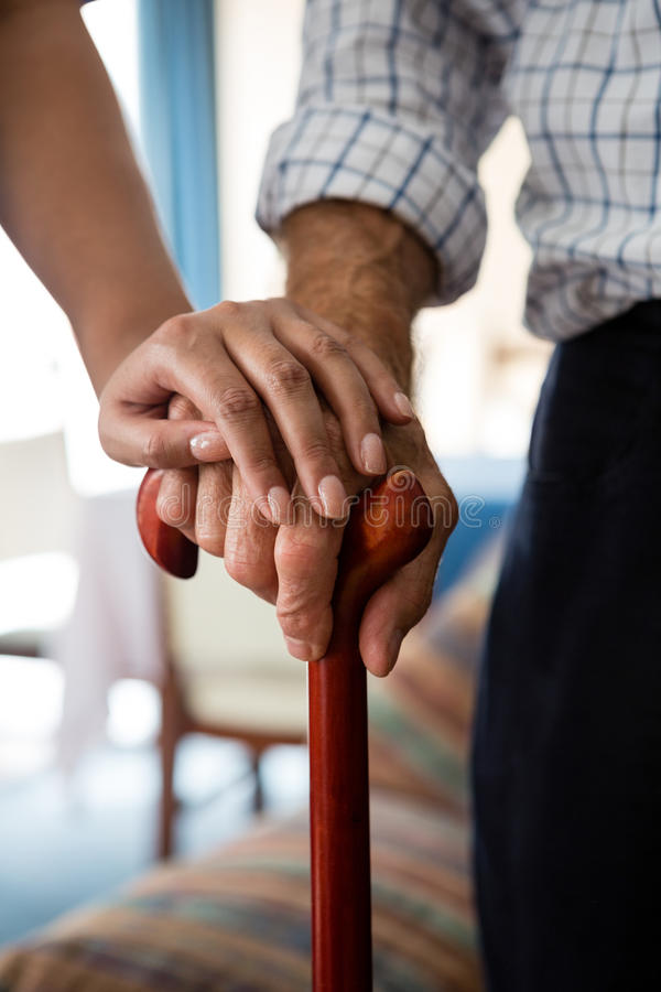 Hands of female doctor and senior man holding walking cane in retirement home stock image