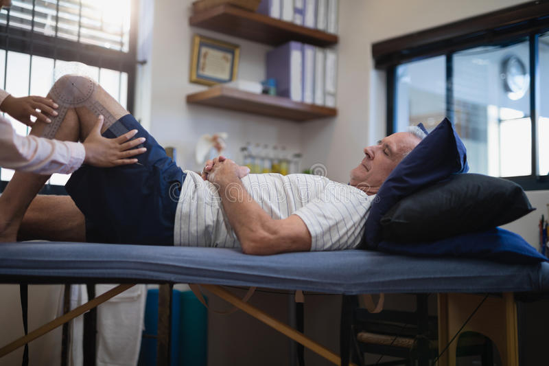 Hands of female therapist measuring knee while senior male patient lying on bed royalty free stock image