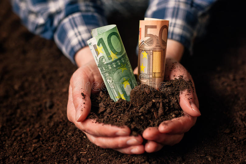 Hands with fertile soil and euro money banknotes royalty free stock photography
