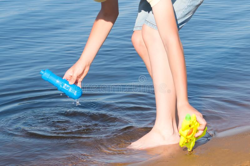 Hands fill the water gun on the river close up royalty free stock photography