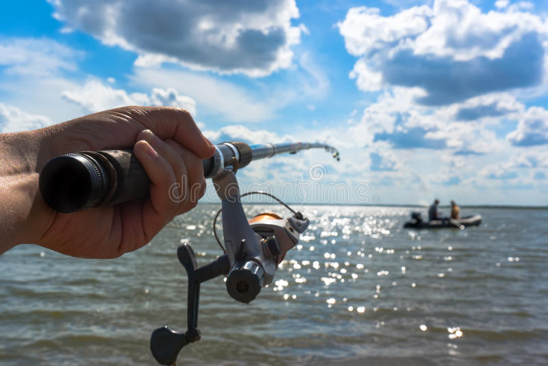 Hands fisherman keep spinning rod royalty free stock images