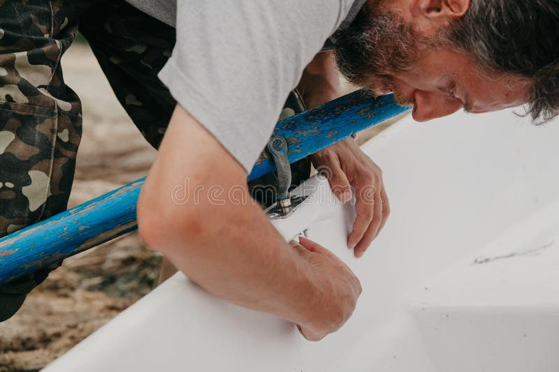 Hands set  paddle on  boat. Hands of the fisherman set the wooden paddle on board the white boat royalty free stock photo