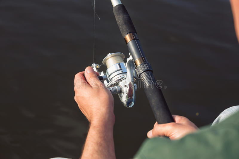 Hands of a fisherman with spinning rod in hand close up stock image