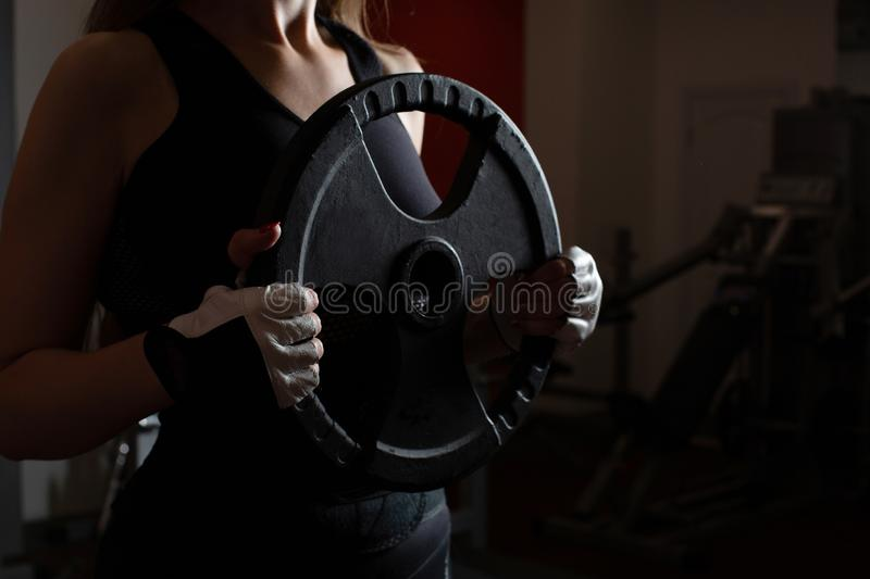 Hands of fitness model holding barbell plates during training. Empty space stock images