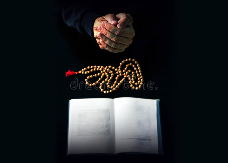 Hands folded in prayer over a Holy Bible stock photography