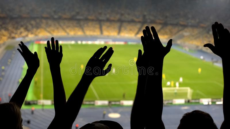 Hands of football fans, cheering team during match on overcrowded stadium royalty free stock image
