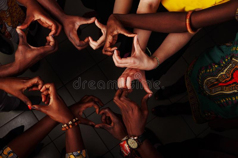 Hands in the form of heart of happy group of multinational African, latin american and european people which stay. Together in circle royalty free stock photos
