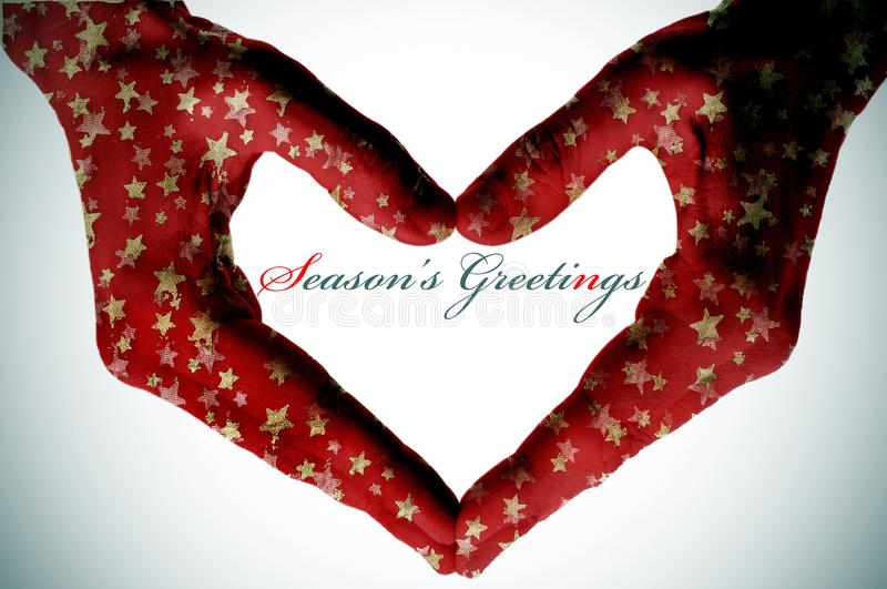 Hands forming a heart and the sentence seasons greetings. Hands patterned with golden christmas stars forming a heart and the sentence seasons greetings royalty free stock photo