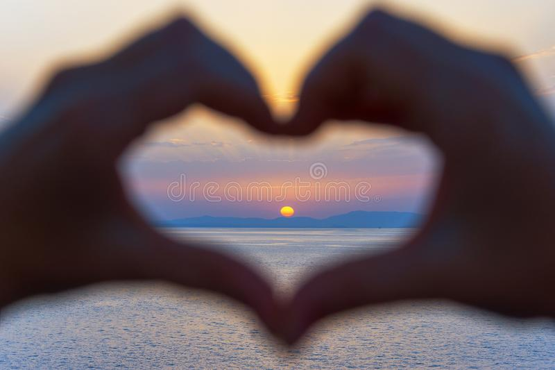 Hands forming a heart shape with sunset stock photos