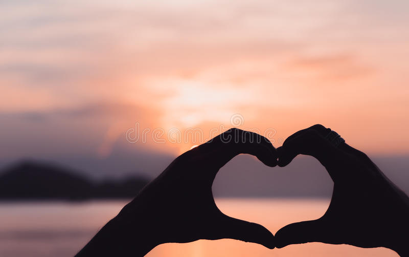 Hands forming a heart shape with sunset stock photography