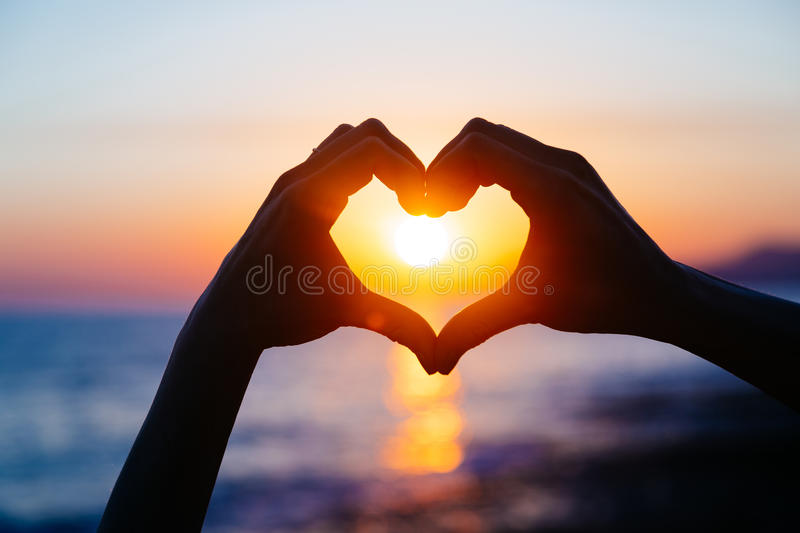 Hands forming a heart shape with sunset silhouette royalty free stock photo