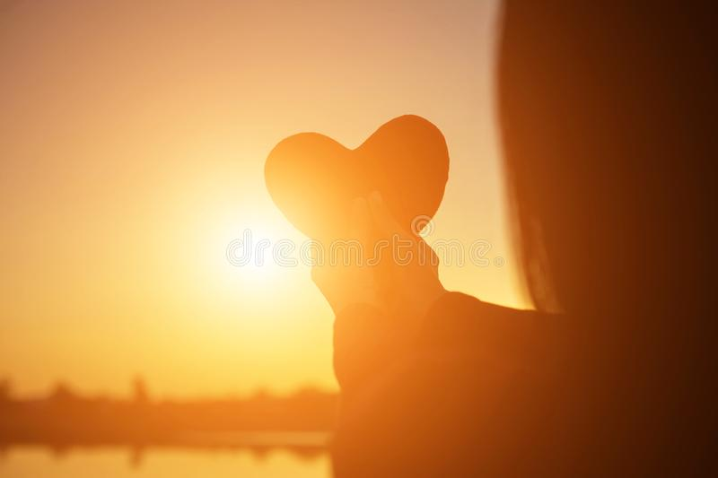 Hands forming a heart shape with sunset silhouette stock image
