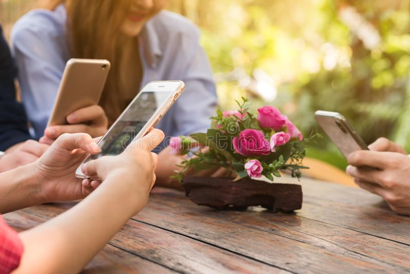 Hands of four teenagers use smartphone together in cafe stock images