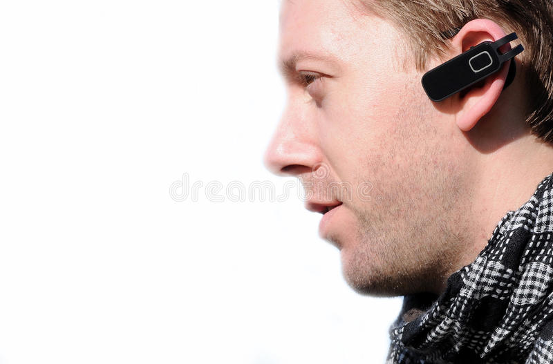 Hands Free. White man communicating using hands-free mobile phone device isolated against white royalty free stock images