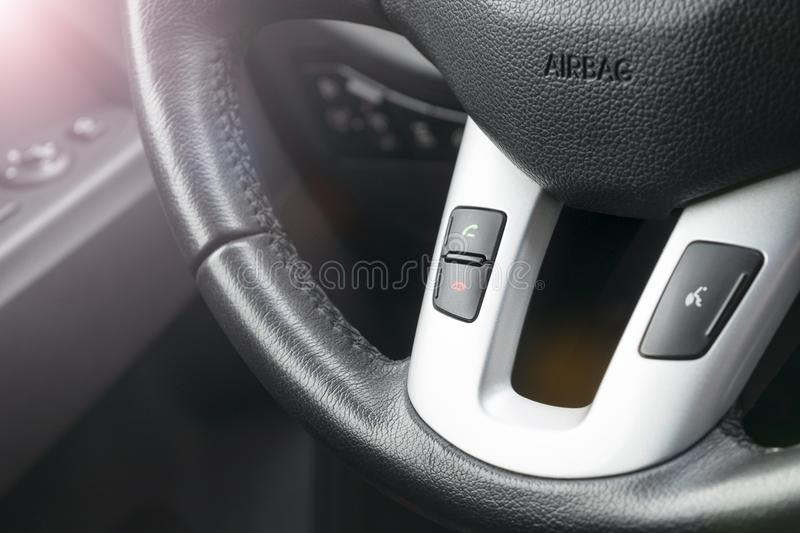 Hands free buttons on the steering wheel in black leather, modern car interior details. Soft lighting. Abstract view. royalty free stock photos