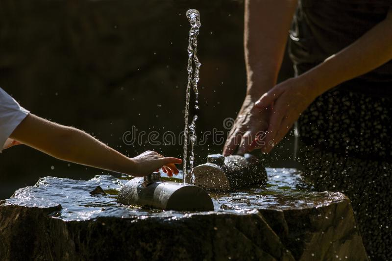 Hands and in fresh, cold, potable source water . Drinking water on hot and sunny summer day. Fresh Potable, Unpolluted, Natural Water. Back light stock photo