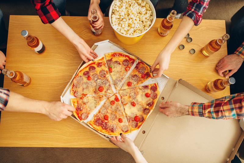Hands of friends taking slices of pizza from table. Hands of friends taking slices of pizza from the table, top view, home party. Good friendship, group of royalty free stock image
