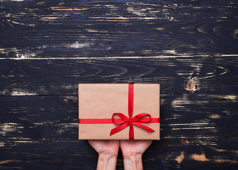 Hands with gift box wrapped in brown paper and tied with red rib. High angle of hands with gift box wrapped in brown paper and tied with red ribbon stock photos