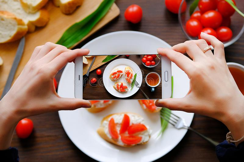 Hands girl bloggers take pictures of Breakfast with your smartphone. Sandwiches, healthy organic products, vegetarian and vegan stock photography