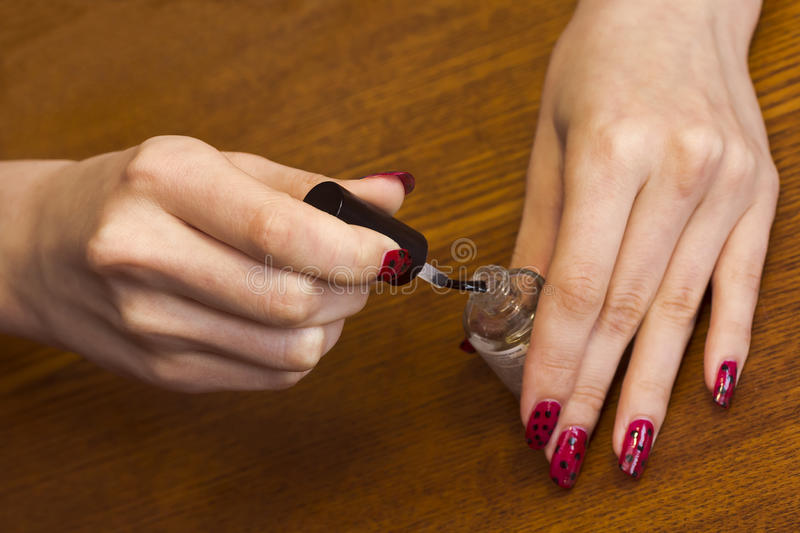 Hands of a girl with a bottle of top coat nail Polish.  royalty free stock images